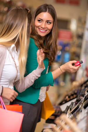 smiling women buying and looking cosmetics in a beauty store