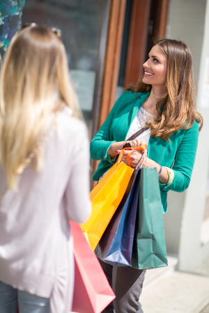 Customer women in shopping street looking at window outdoor Stock Photo