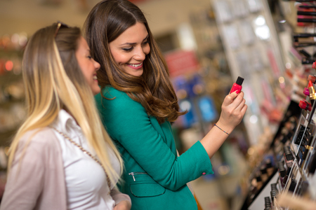 Women buying and looking cosmetics in a beauty store