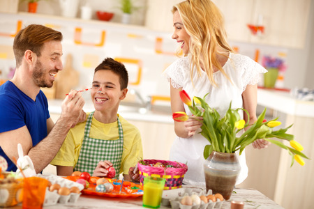 Cheerful father having fun with sun while colored Easter eggs Stock Photo - 103727997
