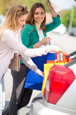 attractive young girls are put the shopping bags into the car trunk