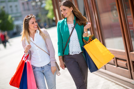 attractive shopaholics with shopping bags walking in the city