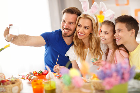 Smiling family making selfie while coloring Easter eggs Stock Photo
