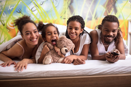 Young family in bed together having fun
