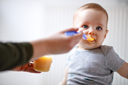 Mother feeds cute male baby with fruit porridge