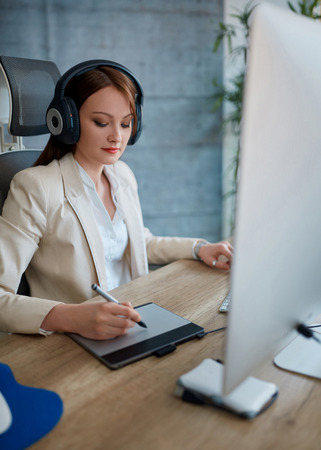 Young woman wearing headphones and working on the pen table Banque d'images - 103671434