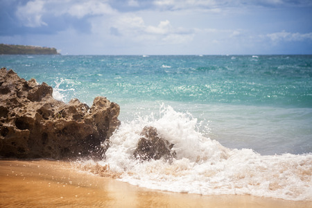 beach with waves crashing against the rocks on the shore Stock Photo