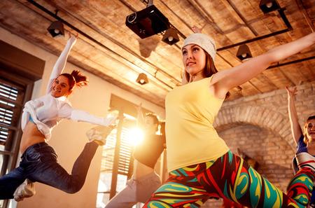 Gruppe von professionellen Leuten, die moderne Tänze trainieren, die während der Musik springen