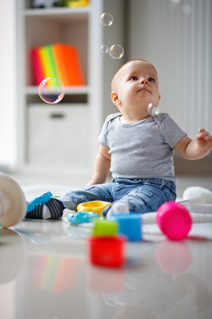 Little boy looking in soap bubbles while sitting on the floor