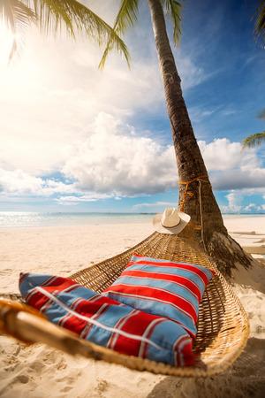 Romantische hangmat in de schaduw van de palm op het tropische strand aan zee Stockfoto