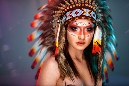 Portrait of young girl in costume native American Indian background