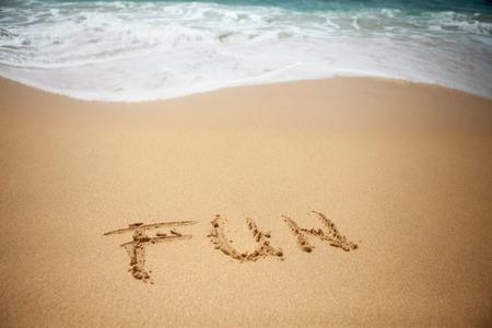 Word FUN hand written on beach with wave