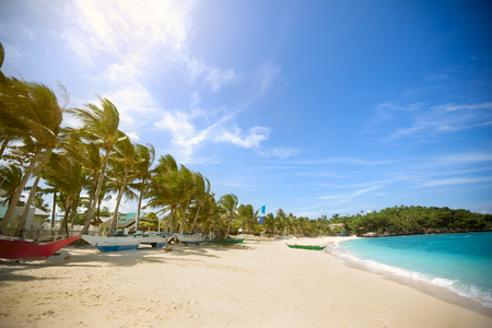 Tropical beach with white sand with boats on it Stock Photo