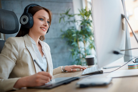 Casual designer woman wearing headphones and working in design studio Banque d'images - 105060807