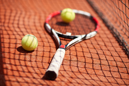 Tennis racket and balls on red clay