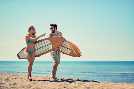 Happy man and woman surfers walking on the beach Imagens