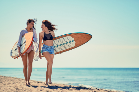 Smiling surfers girls on beach having fun in summer Vacation. Extreme Sport