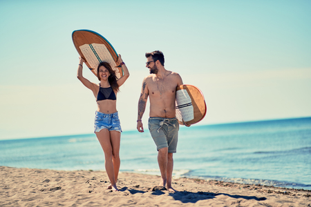 Happy couple of surfers walking at the beach Vacation. Extreme Sport