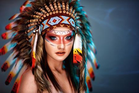 羽の背景の大きなアメリカインディアンプルームを持つ美しい若い女性