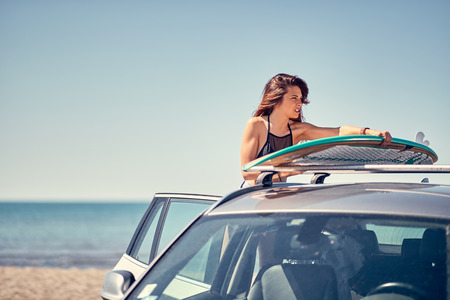Summer holiday road trip vacation- Young smiling surfer girl at the beach with her surfboard on car Vacation. Extreme Sport