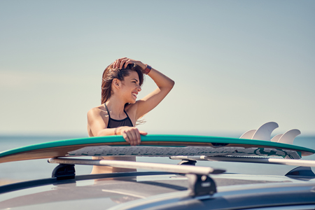 Summer holiday road trip vacation- Young surfer girl at the beach with her surfboard on car