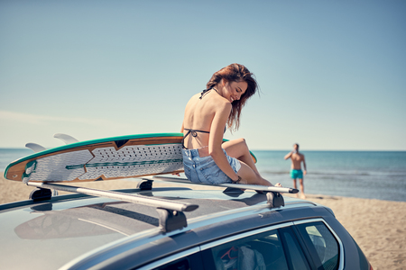 beautiful surfer girl sitting on the car and getting ready for surfing