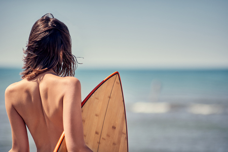 Surfer girl. Sexy young woman at the beach. -Back view Stock Photo