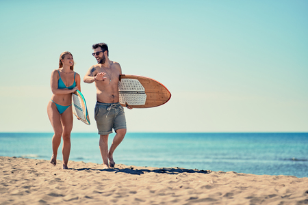 Smiling young couple of surfers walking on the beach 写真素材