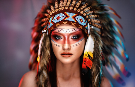 American Indian girl in native costume, headdress made of feathers of wild birds