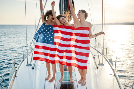 Sexy smiling young girls on the yacht in American flag