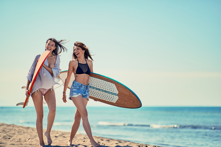 Attractive girl's outdoors -Young surfers on the beach