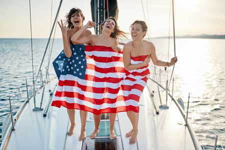 Sexy happy young girls on the yacht in American flag
