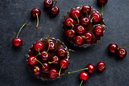 ripe red cherry in a chocolate tart on dark grunge background