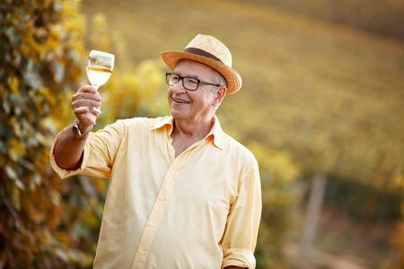 Happy winegrower tasting white wine in vineyard Stock Photo