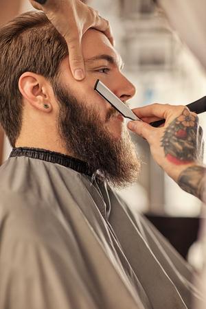 Barber with razor shaving bearded man