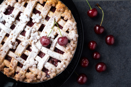 pie with cherries, icing sugar, black plate and fresh cherries