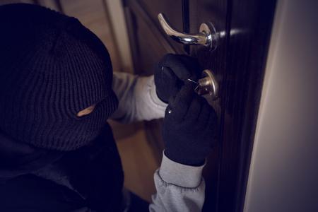 burglar breaking into the lock on the front door