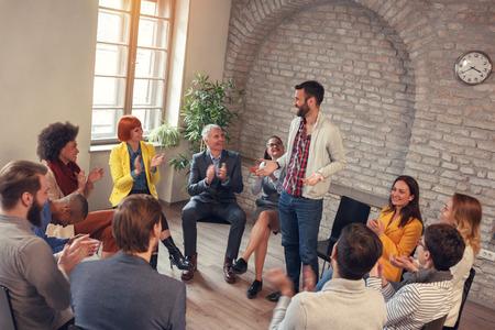Businessman smiling in group meeting- coworkers applauding man in group