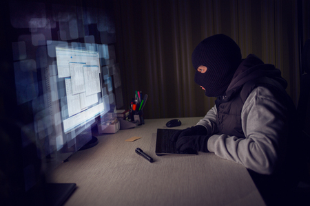 Computer hacker stealing data from a computer,  concept for network security, identity theft and computer crime.
