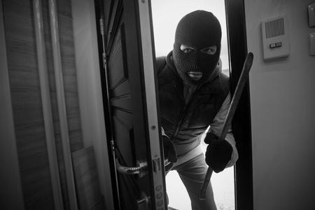 Burglar breaking door of house with crowbar