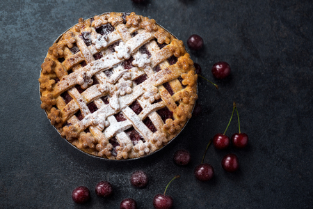 homemade cherry pie with a flaky crust and sprinkles powdered sugar