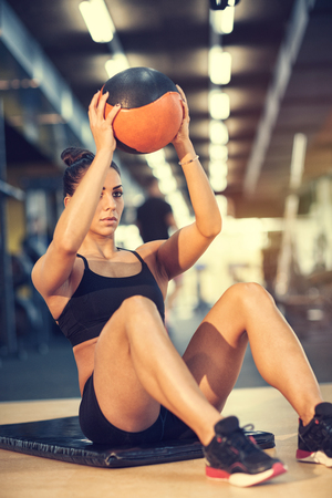 Fit sportswoman doing exercise with ball for six pack 스톡 콘텐츠