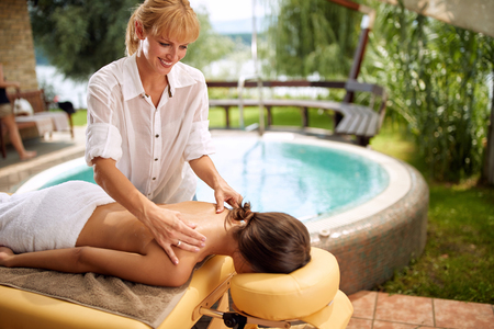 Smiling massage therapist doing a back massage at home Stock Photo - 108571417