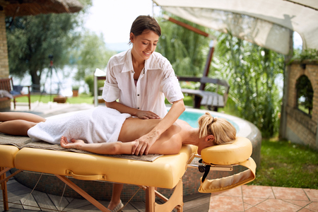 Relaxed woman receiving back massage in wellness center on outdoor