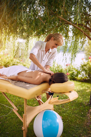 Back Massage-Woman at the spa getting a relaxed massage in nature Stock Photo - 108581117