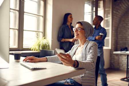 Smiling girl at workplace operates on computer and listen music on cell phone