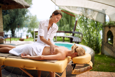 Spa massage - Beautiful woman in spa salon on outdoor getting massage Stock Photo - 108581118