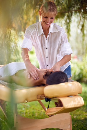 Massage therapy, healthcare concept, young woman lying on massage bed receiving a treatment from a masseur in nature Stock Photo - 108581570