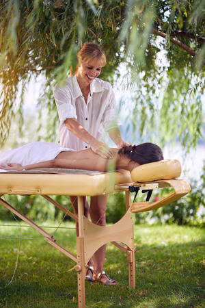 Massage therapy, healthcare concept, young female lying on massage bed receiving a treatment from a professional masseur Stock Photo