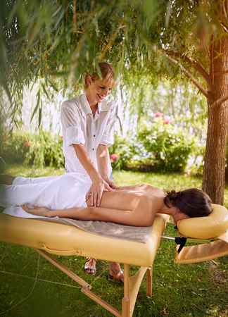 Smiling massage therapist doing a back massage woman in nature